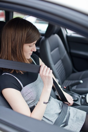 Road safety concept - Pretty young woman fastening her seat belt in a car Stock Photo - 9799756