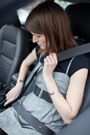 Road safety concept - Pretty young woman fastening her seat belt in a car photo