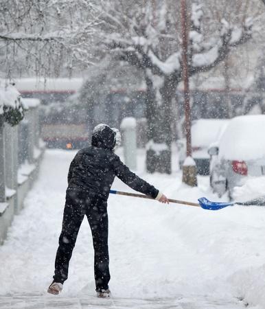 plowing: Mujer paleaban nieve desde una acera despu�s de una fuerte Nevada en una ciudad