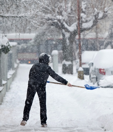 Woman shoveling snow from a sidewalk after a heavy snowfall in a city photo