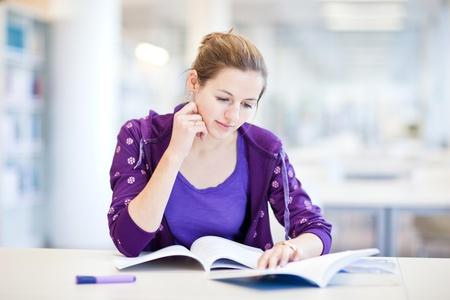 Teenagers studying: bastante joven estudiante en una biblioteca (DOF superficial; imagen en tonos de color)