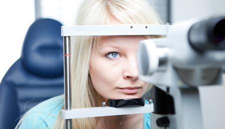 optometria: Optometria koncepcji - całkiem młoda kobieta o jej oczu zbadane przez lekarza oka na lampa szczelinowa