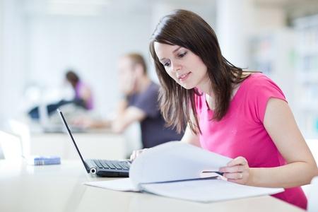 adolescentes estudiando: en la biblioteca - guapa estudiante femenina con port�tiles y libros en una biblioteca de la escuela secundaria (tonos de color de imagen)