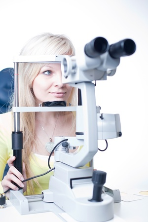 doctor of optometry: optometry concept - pretty young female patient having her eyes examined by an eye doctor Stock Photo