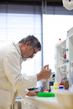 senior male researcher carrying out scientific research in a lab (shallow DOF; color toned image) Stock Photo - 9800138