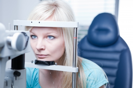 eye test: optometry concept - pretty young female patient having her eyes examined by an eye doctor Stock Photo