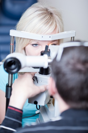doctor of optometry: optometry concept - pretty young female patient having her eyes examined by an eye doctor (color toned image; shallow DOF)