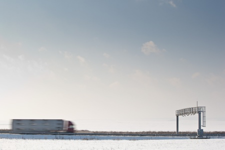 truck passing trhough a toll gate on a highway (motion blurred image; color toned image)
