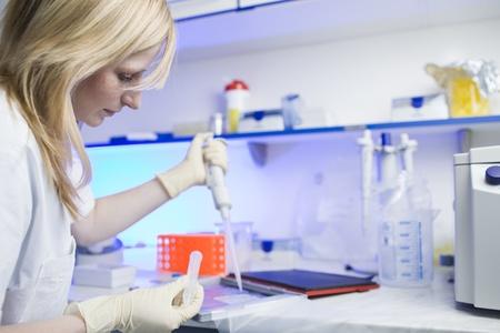 pipette: Retrato de un investigador femenino haciendo investigaci�n en un laboratorio (color en tonos imagen; DOF superficial)