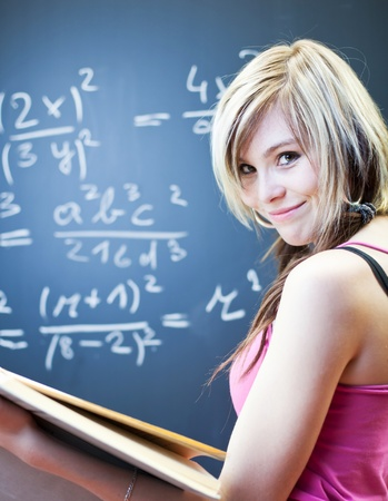 pretty young college student writing on the chalkboardblackboard during a math class  photo