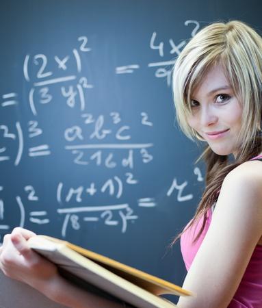 matematica: bastante joven estudiante escribir en la pizarrapizarra durante una clase de matem�ticas (DOF superficial; imagen en tonos de color)