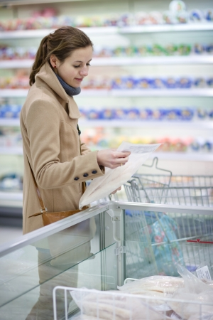 pretty youman buying groceries in a supermarket/mall/grocery store - frozen fish(color toned image; shallow DOF) Stock Photo - 9902466