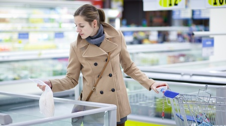 pretty youman buying groceries in a supermarket/mall/grocery store - frozen fish(color toned image; shallow DOF) Stock Photo - 9807842