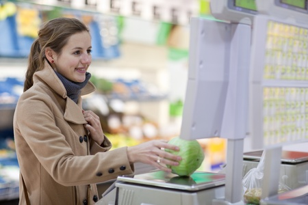 Beautiful young woman shopping for fruits and vegetables in produce department of a grocery storesupermarket (shallow DOF; color toned image) photo