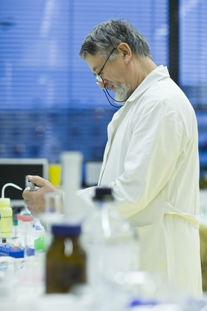 chromatograph: senior male researcher carrying out scientific research in a lab using a gas chromatograph