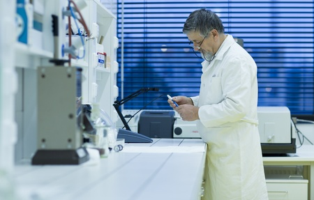 health care research: senior male researcher carrying out scientific research in a lab using a gas chromatograph