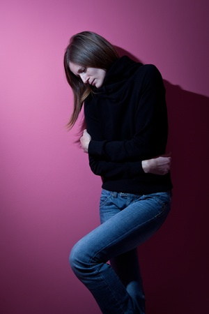 Young woman suffering from a severe depression/anxiety (color toned image; harsh lighting is used to convey the mood of unease) Stock Photo - 9808017