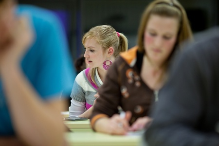 pretty female college student sitting in a classroom full of students during class (shallow DOF; color toned image) photo