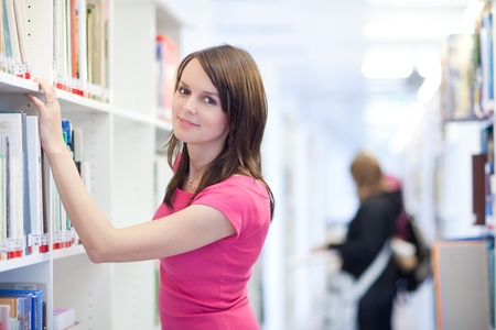 pretty young college student in an university library (shallow DOF; color toned image) Stock Photo - 9901340