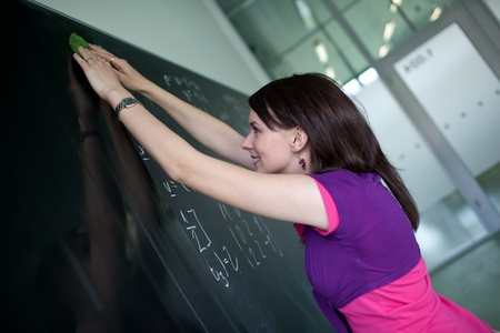 pretty young college student writing on the chalkboardblackboard during a math class (shallow DOF; color toned image) photo
