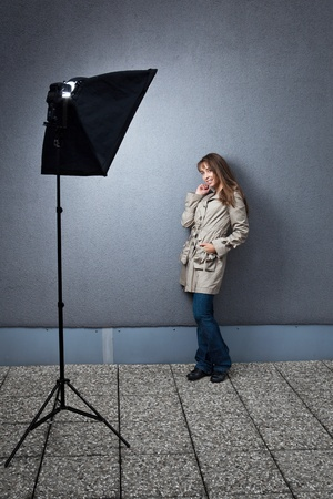 Pretty young female caucasian model being photographed on location - lit by a strobe in a softbox photo