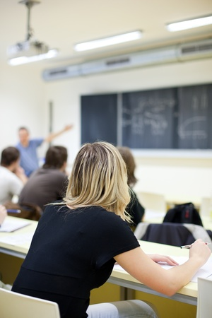 young pretty female college student sitting in a classroom full of students during class (shallow DOF; color toned image) Stock Photo - 9807899