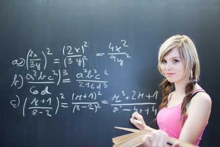 tutor: bastante joven estudiante escribir en la pizarrapizarra durante una clase de matem�ticas (DOF superficial; imagen en tonos de color)