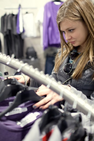 pretty teenager shopping for clothes in a boutique/fashion shop/store (shallow DOF) photo