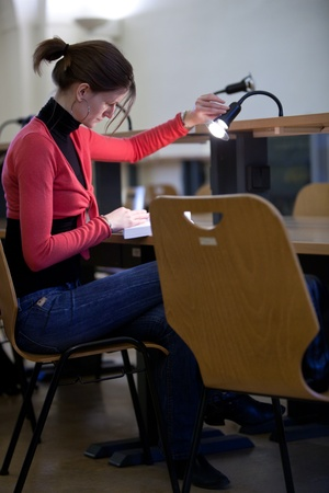 pretty female college student in a college library (shallow DOF; color tuned image) photo
