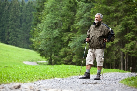 active handsome senior man nordic walking outdoors on a forest path, enjoying his retirement Stock Photo - 9816847