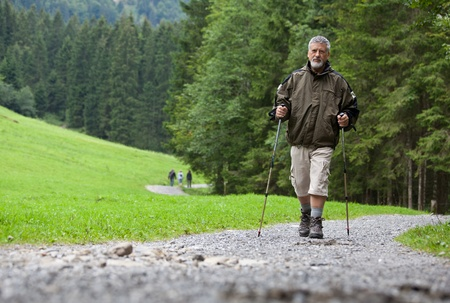 action fund: active handsome senior man nordic walking outdoors on a forest path, enjoying his retirement Stock Photo