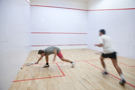 match: Squash players in action on a squash court (motion blurred image; color toned image) Stock Photo