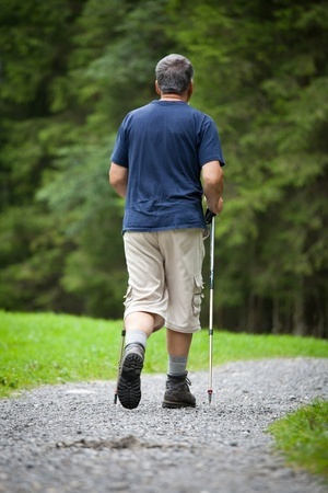 active handsome senior man nordic walking outdoors on a forest path, enjoying his retirement Stock Photo - 9816805