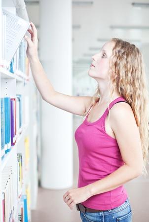 pretty female college student in a library Stock Photo - 9804245