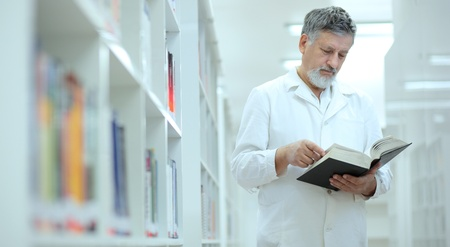 Renowned scientist/doctor in a library of research center/hospital - browsing a book