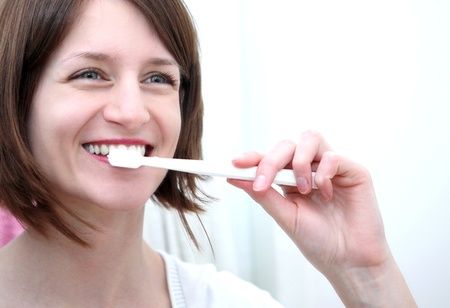 Dental Hygiene Concept - A close-up view of a beautiful woman brushing her teeth photo