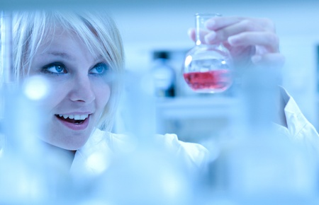 Closeup of a female researcher carrying out experiments in a laboratory - looking surprised Stock Photo - 9794512
