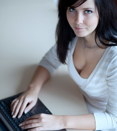 sexy office girl: pretty young brunette workingtyping on a laptop computer in a officeclassroom