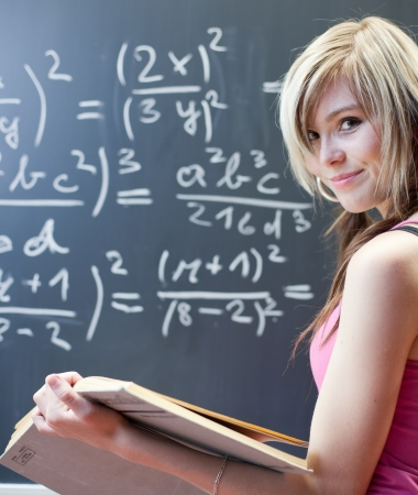 mathematic: pretty young college student writing on the chalkboardblackboard during a math class