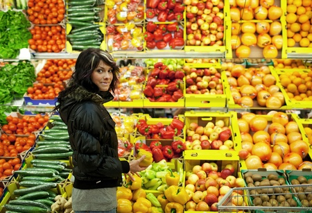 Beautiful young woman buying fruits and vegetables at a supermarketgrocery photo