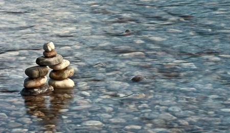 tranquilityspiritual balance concept - pebble pyramid in a river  photo