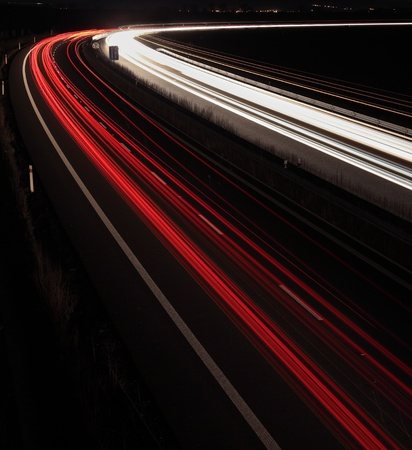 Night highway (Cars in a rush moving fast on a highway  (speedway) in the UK at the nightfall photo