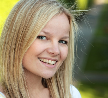 sweetly: Closeup portrait of a beautiful young blond woman smiling sweetly while in a park