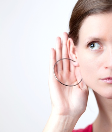 Pretty young woman puts her hand to her ear and listens attentively Stock Photo - 9794354