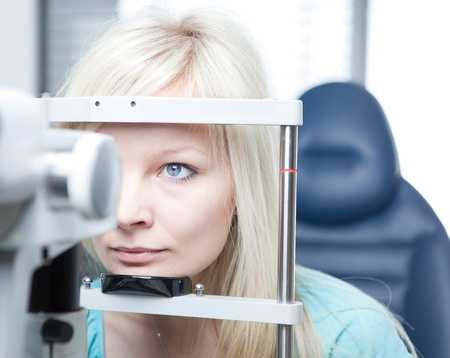 optometry concept - pretty young woman having her eyes examined by an eye doctor on a slit lamp photo