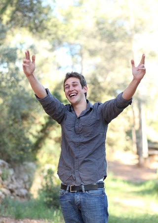 energetically: elated handsome young man expressing his joycontentdelight energetically in a park outdoors Stock Photo