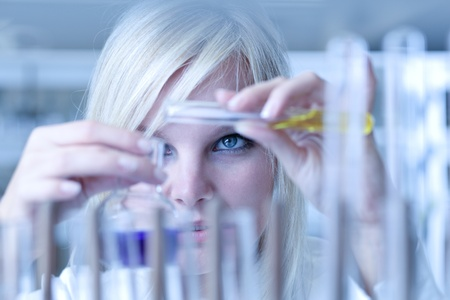 scientific experiment: Closeup of a female researcher holding up a test tube and a retort and carrying out experiments (color toned image) Stock Photo