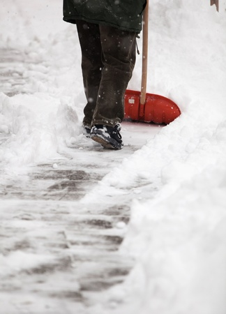 Man shoveling snow from the sidewalk in front of his house after a heavy snowfall in a city photo