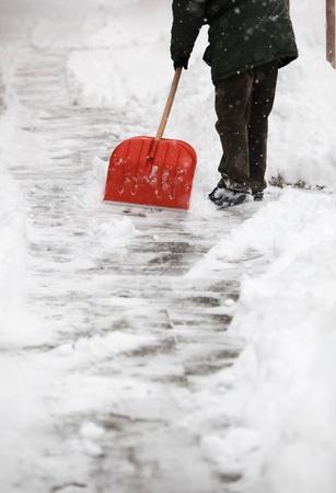 plowing: El hombre quitando la nieve de la acera de enfrente de su casa despu�s de una fuerte nevada en una ciudad