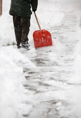 schneesturm: Man shoveling snow from the sidewalk in front of his house after a heavy snowfall in a city